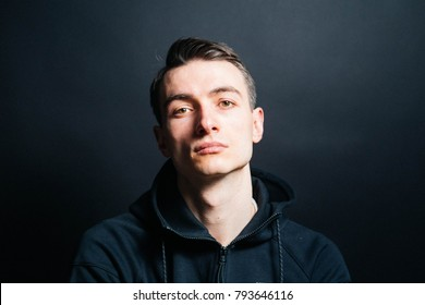 Color portrait of a young man in a black sweatshirt, looking at the camera, against plain studio background