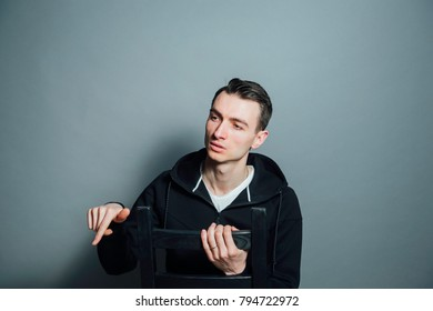Color portrait of a young man in a sweatshirt, looking to the side while explaining smth, against plain studio background