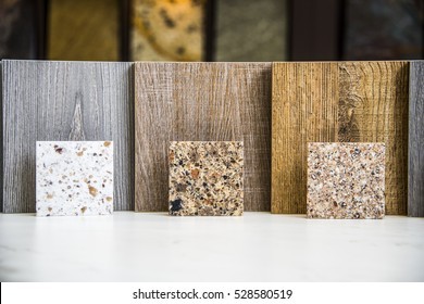Color samples of granite, marble and quartz kitchen countertops lined up on stone island