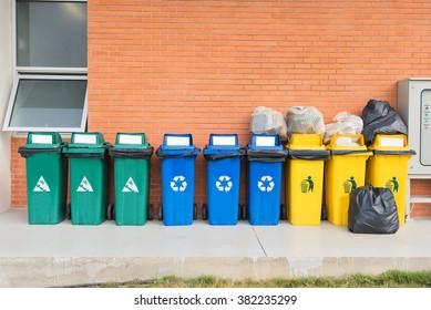 Color set garbage plastic bins on brick background