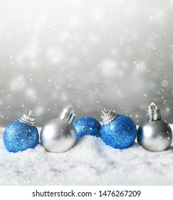 Color shiny christmas balls in snow background.