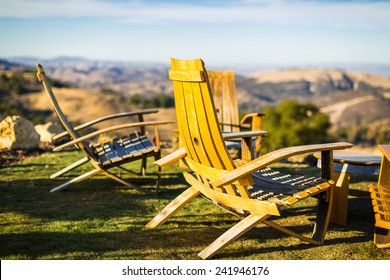 Color shot of adirondack chairs on green grass overlooking Paso Robles wine country at a winery in California