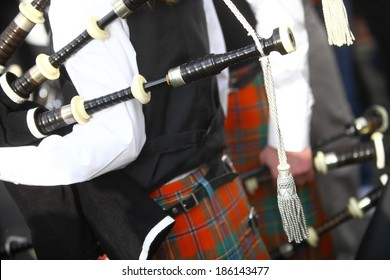Color shot of a person holding a traditional bagpipe.
