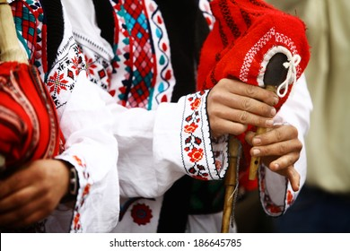 Color shot of a person holding a traditional Romanian bagpipe.