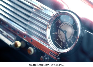 Color shot of a vintage clock on a car's dashboard.