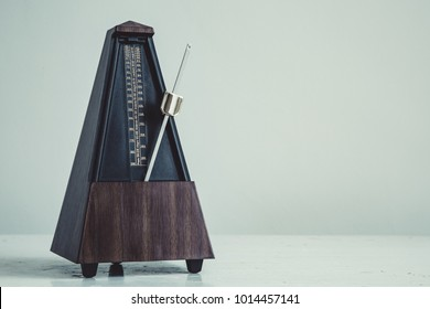 Color shot of a vintage metronome, on gray background.