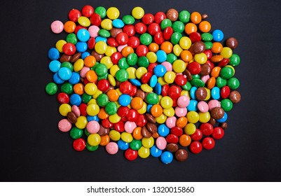 Color small chocolate dragee. Candy on a black background. Close-up.