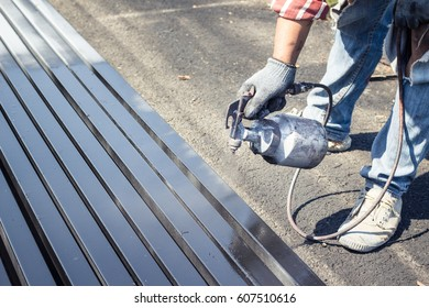 color spray painter working with metal structure