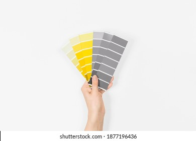 Color swatches with colors of the year 2021 in the hand - Illuminating and Ultimate Grey. Color trend palette. Top view, flat lay.