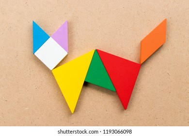 Color tangram puzzle in cat shape on wood background