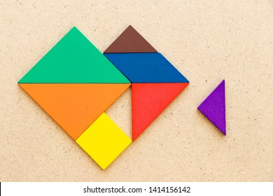 Color tangram puzzle in heart shape that wait triangle piece to fulfill on wood background