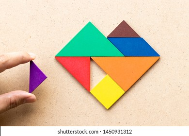 Color tangram puzzle in heart shape that wait triangle piece to fulfill shape on wood background