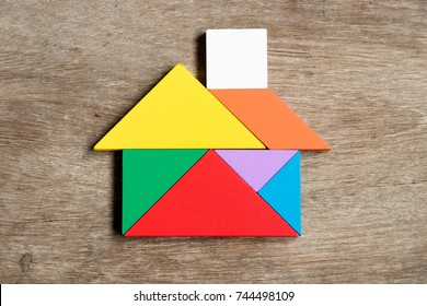 Color tangram puzzle in house shape on wood background