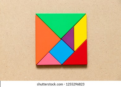 Color tangram puzzle in square or rectangle shape on wood background