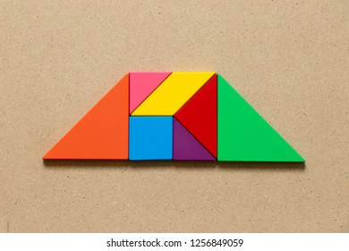 Color tangram puzzle in trapezoid  shape on wood background