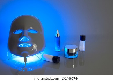 Color therapy mask glowing blue with creams
