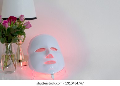 Color therapy mask glowing red on table