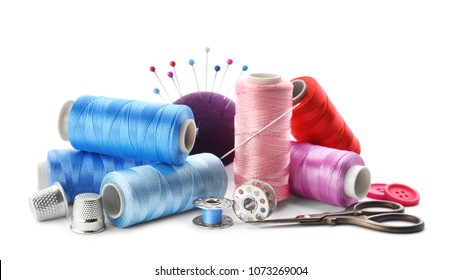 Color threads and sewing accessories on white background