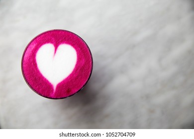Color trendy beetroot latte is on white table. It is heart art on the top of the latter
