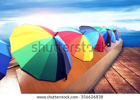 8ca965157 color umbrella with blur dark clouds on blue sky and flare light background