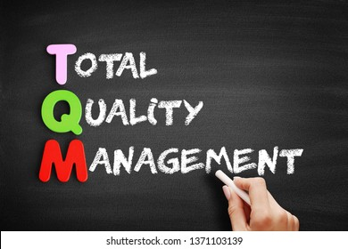 Color Wooden alphabets building the word TQM - Total Quality Management acronym on blackboard