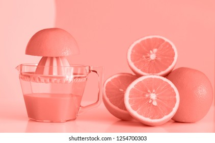 Color of the year 2019 Living Coral. Freshly squeezed orange juice and orange on Living Coral background. Health cocept.
