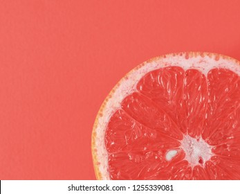 Color of year 2019 Living Coral concept. Grapefruit half on living coral background. Top view or flat lay. Copy space for text.