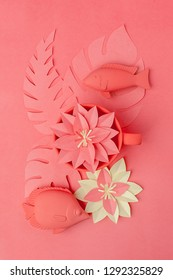 color of the year 2019 living coral concept. Fish toys set  and origami papercraft flowers, branches on living coral background, monochrome minimal vacation summer concept