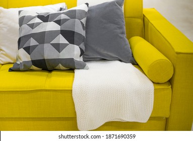 Color of the year 2021. blanket and pillows on the sofa in the interior. Color 2021 illuminating and Ultimate Gray.