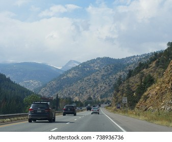 COLORADO, USA—OCTOBER 2017: Scenic view of winding road and cars running along Interstate 70 in the Colorado Rockies, with directional speed limit sign on the roadside.