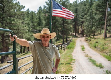 A colorado cowboy stands with his hand on a green metal gate with the  American Flag in the background. He is wearing a straw cowboy hat and a t-shirt.