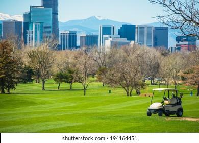 Colorado Golf Field with Denver Skyline and Golf Cart.