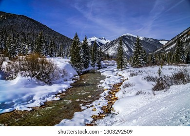 Colorado mountain valley after freshly fallen snow covering trees and mountain peaks with water flowing in river