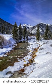 Colorado Mountain valley off of Red Mountain Pass with water flowing in river and cover of freshly fallen snow on sunny blue sky day