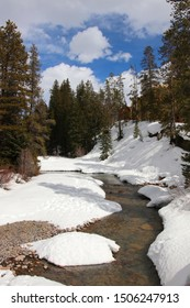 Colorado snowy early spring beautiful nature background. Scenic view with water stream on a covered by snow valley between rocky mountains. Amazing Keystone landscape, Colorado, USA.