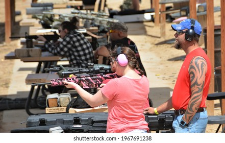 Colorado Springs, CO. USA. April 25, 2021. Unidentified Husband watching his wife shoot her pink AR-15 at Dragon Mans shooting range. Target shooting is a very popular sport.