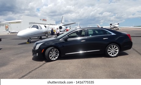 COLORADO SPRINGS, COLORADO - JUNE 5, 2019: A Black Cadillac XTS parked by a private jet