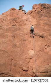 Colorado Springs, Colorado, USA: April 4, 2016 Garden of the Gods is a popular location for rock climber woman rappelling down red sandstone cliffs