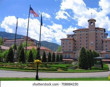 Colorado Springs, Colorado USA - May 31, 2008: The Broadmoor Resort Italian Renaissance main building and entrance landscaping from Lake Avenue under bright sky. Celebrating 100th anniversary.