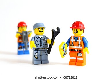 Colorado, USA - April 17, 2016: Studio shot of LEGO minifigure construction workers having a discussion with a mechanic, isolated on white background.