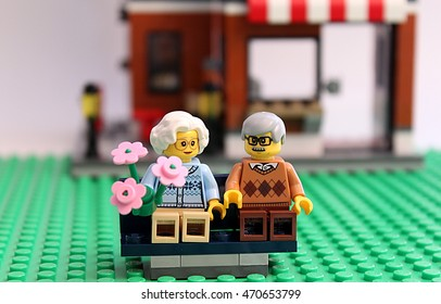 Colorado, USA - August 18, 2016: Studio shot of LEGO minifigure old couple sitting on park bench with woman holding flowers.