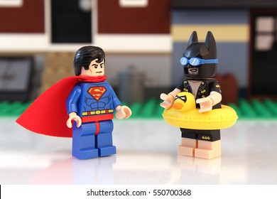 Colorado, USA - January 7, 2017: Studio shot of LEGO Batman and Superman oustide a building talking while Batman is ready for swimming with a plastic duck floaty,