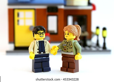 Colorado, USA - July 16, 2016: Studio shot of LEGO guy and girl holding hands in front of doorway to their new home. Shot isolated on white background.