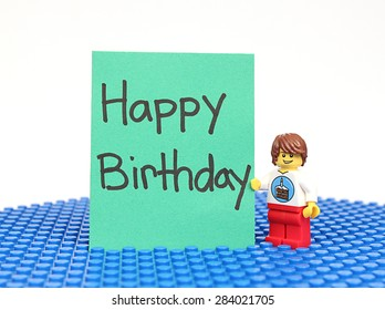 Colorado, USA - June 1, 2015: Studio shot of Lego minifigure with Happy Birthday sign. Legos are a popular line of plastic construction toys manufactured by The Lego Group, a company based in Denmark.