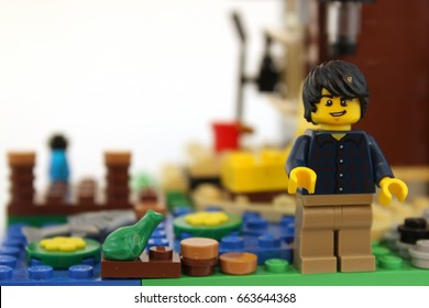 Colorado, USA - June 14, 2017: Studio shot of cute LEGO minifigure guy standing by a pond with a frog.