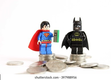 Colorado, USA - March 25, 2016: Studio shot of LEGO minifigure Batman and Superman standing on a pile of money.
