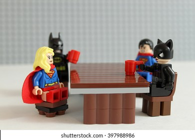 Colorado, USA - March 25, 2016: Studio shot of LEGO minifigure Batman, Superman, Supergirl, and Catwoman sitting around a table together.