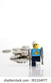 Colorado, USA - March 9, 2016: Studio shot of LEGO minifigure injured man with crutches leaving behind a trail of money. Photo isolated on white background.