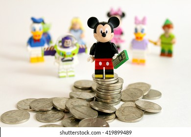 Colorado, USA - May 13, 2016: Studio shot of LEGO minifigure Mickey Mouse on top of a pile of money with other Disney characters in the background. Photo isolated on white.
