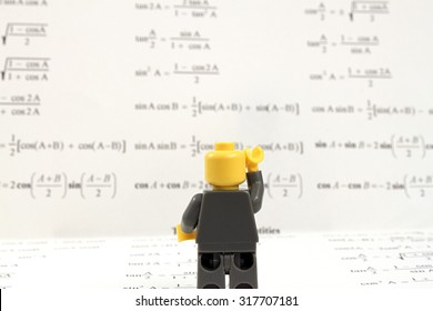 Colorado, USA - September 17, 2015: Studio shot of confused Lego minifigure staring at and standing on math formulas.